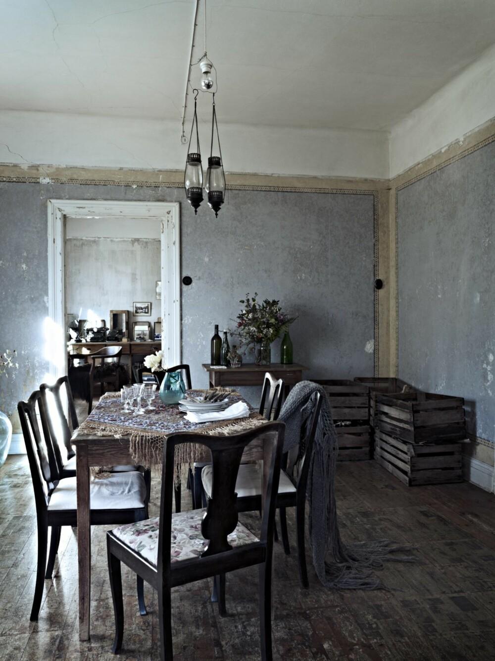 HISTORIE I VEGGER OG GULV: Under gulvbelegget i spisestuen lå det gamle aviser som isolasjon. Avisene hadde satt avtrykk på plankene under. For å bevare avtrykkene, ble gulvet behandlet med klarlakk. Spisebordet er et loppemarkedfunn som Christina fikk for 10 kroner.