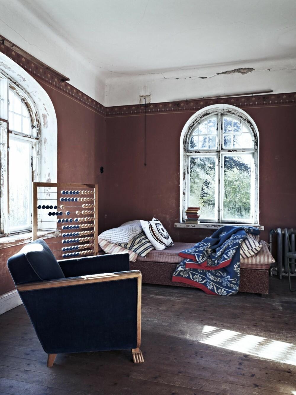 KONTRASTER: De friske tekstilene i dagsengen i den ene stuen er en fin motvekt til de patinerte veggene. Den store kulerammen i tre er nok et bruktfunn.