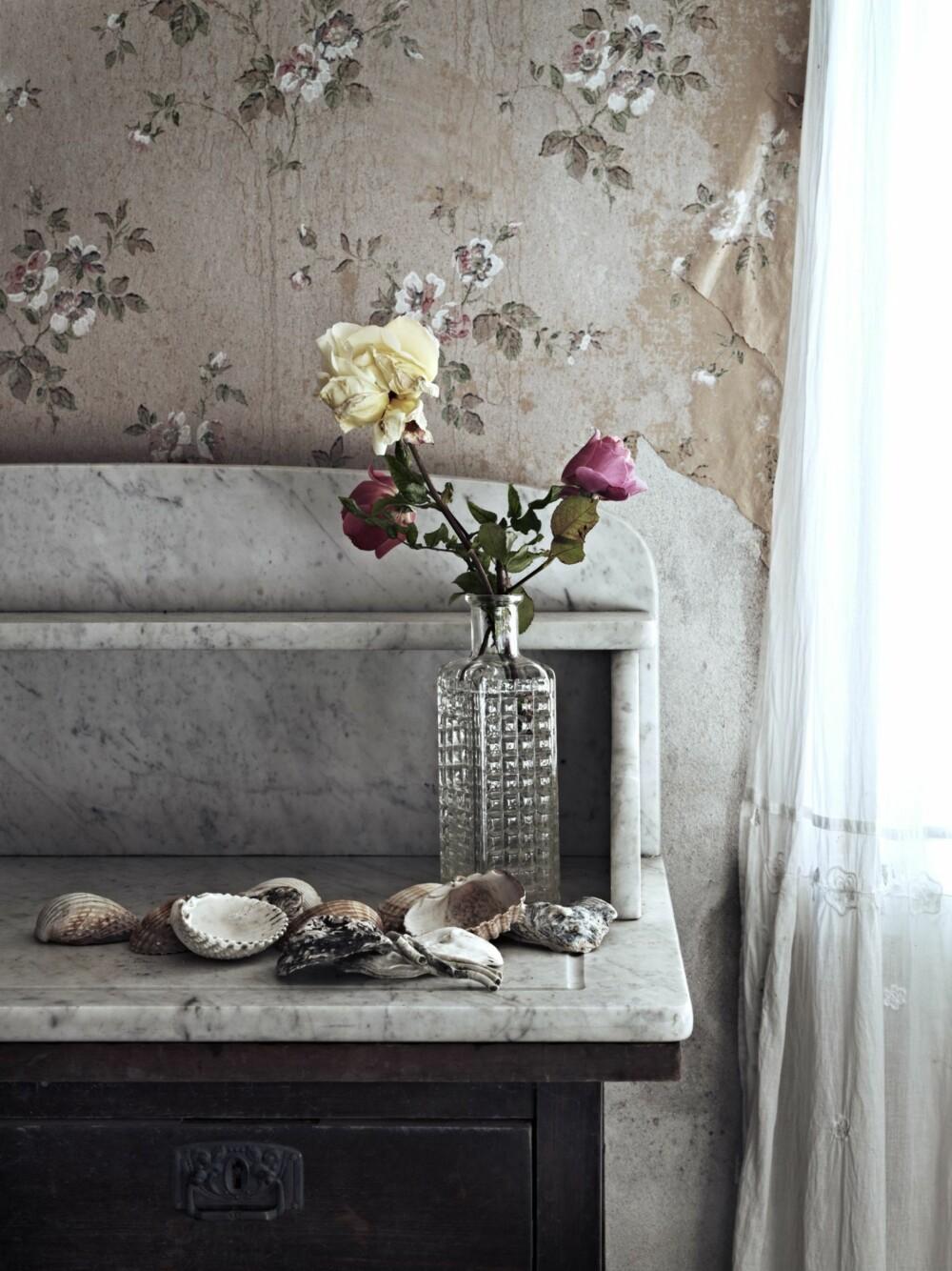 VAKRE DETALJER: Små stilleben med friske blomster og skjell frisker opp det gamle tapetet med blomstermønster.
