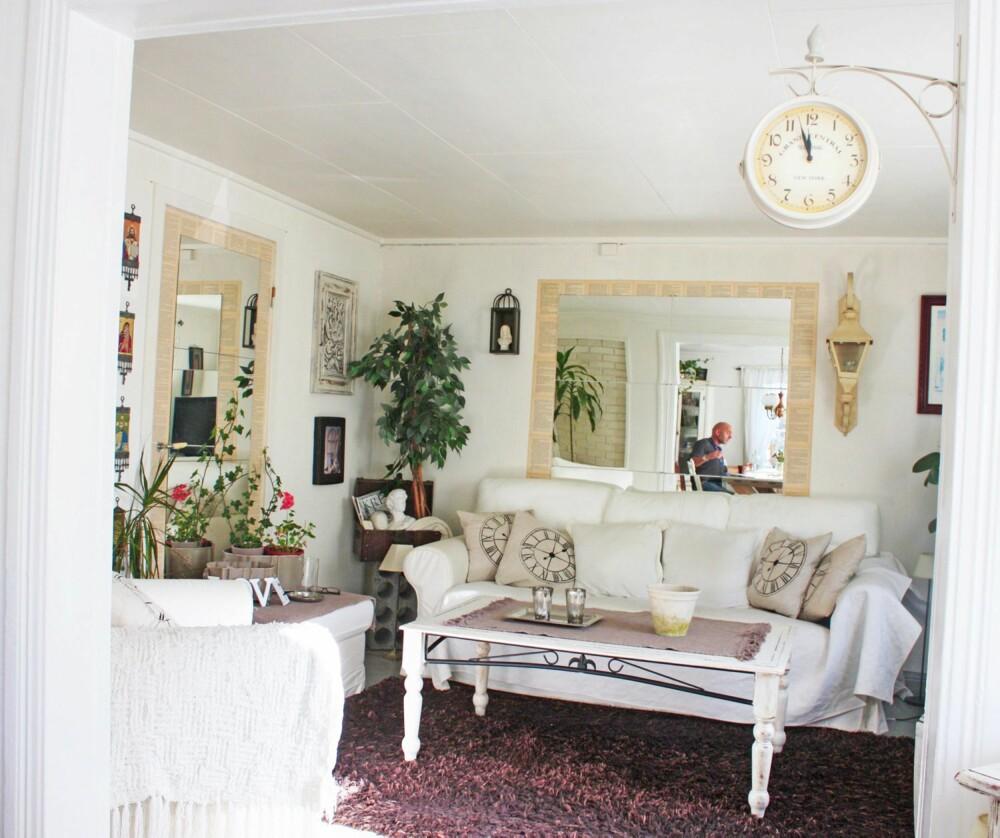 SPEIL PÅ VEGGEN DER: Et speil øker romfølelsen i stuekroken, som ellers er pyntet slik et shabby hjem skal pyntes, med bokstaver, blomster og en nostalgisk klokke.