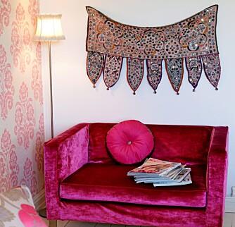 """INNBYDENDE: Sofaen """"Square Chair"""" i rosa chenille kommer fra Designers Child og Riis Interiør. Indisk teppe på veggen lager atmosfære."""