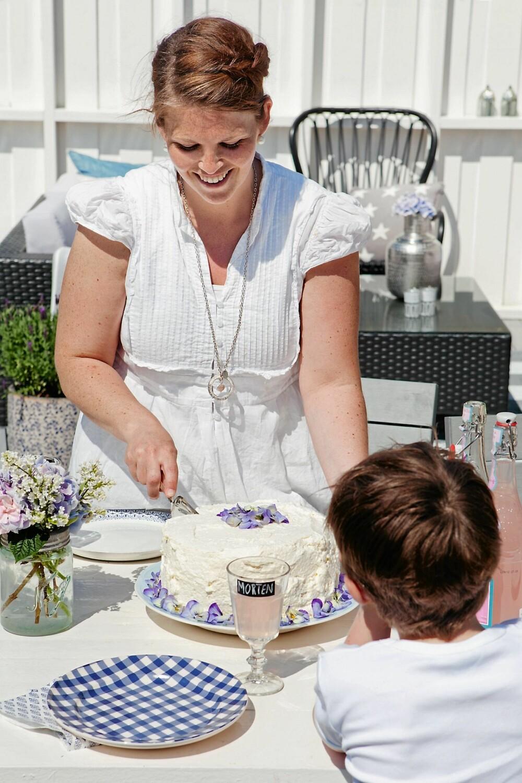 FIOLER ER BLÅ: Hanne Mette har pyntet bløtkaken med spiselige fioler, og gitt den en sommerlig vri. Morten gleder seg.