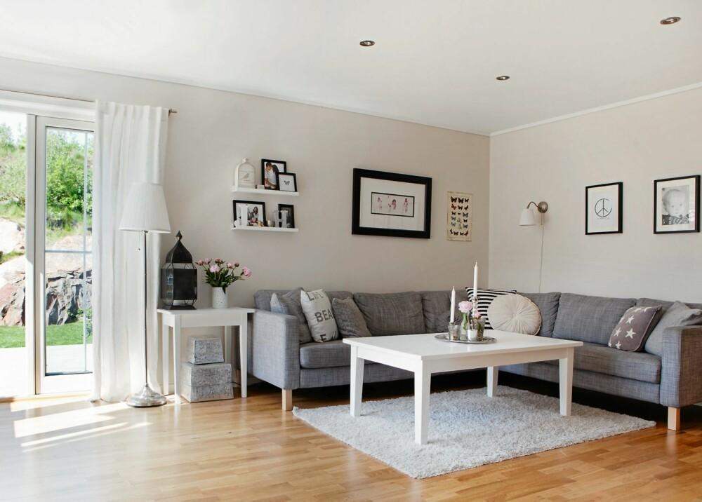 RENE LINJER: Stuen er klassisk og enkel, medi kjølige grå og hvite toner. Eikegulvet varmer opp, sammen med familiebilder og stearinlys. Sofaen er fra Ikea.