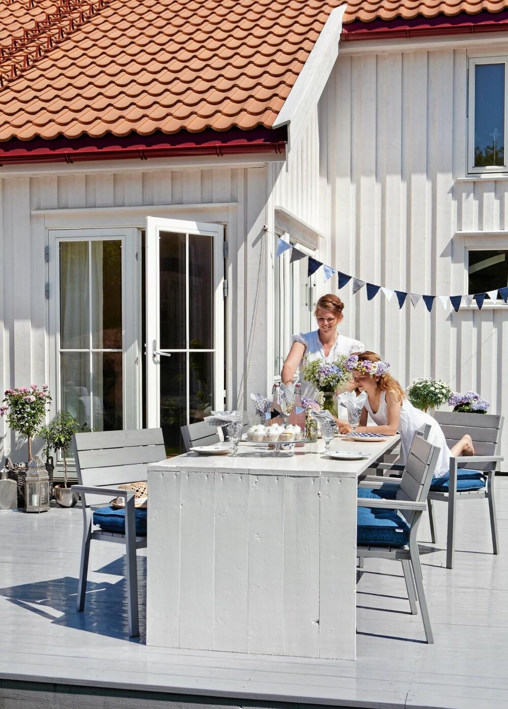 DEKKET TIL FEST: Hanne Mette Huseby elsker å pynte opp ute så vel som inne. Egenlagde vimpler gjør hverdagen til fest i en fei.