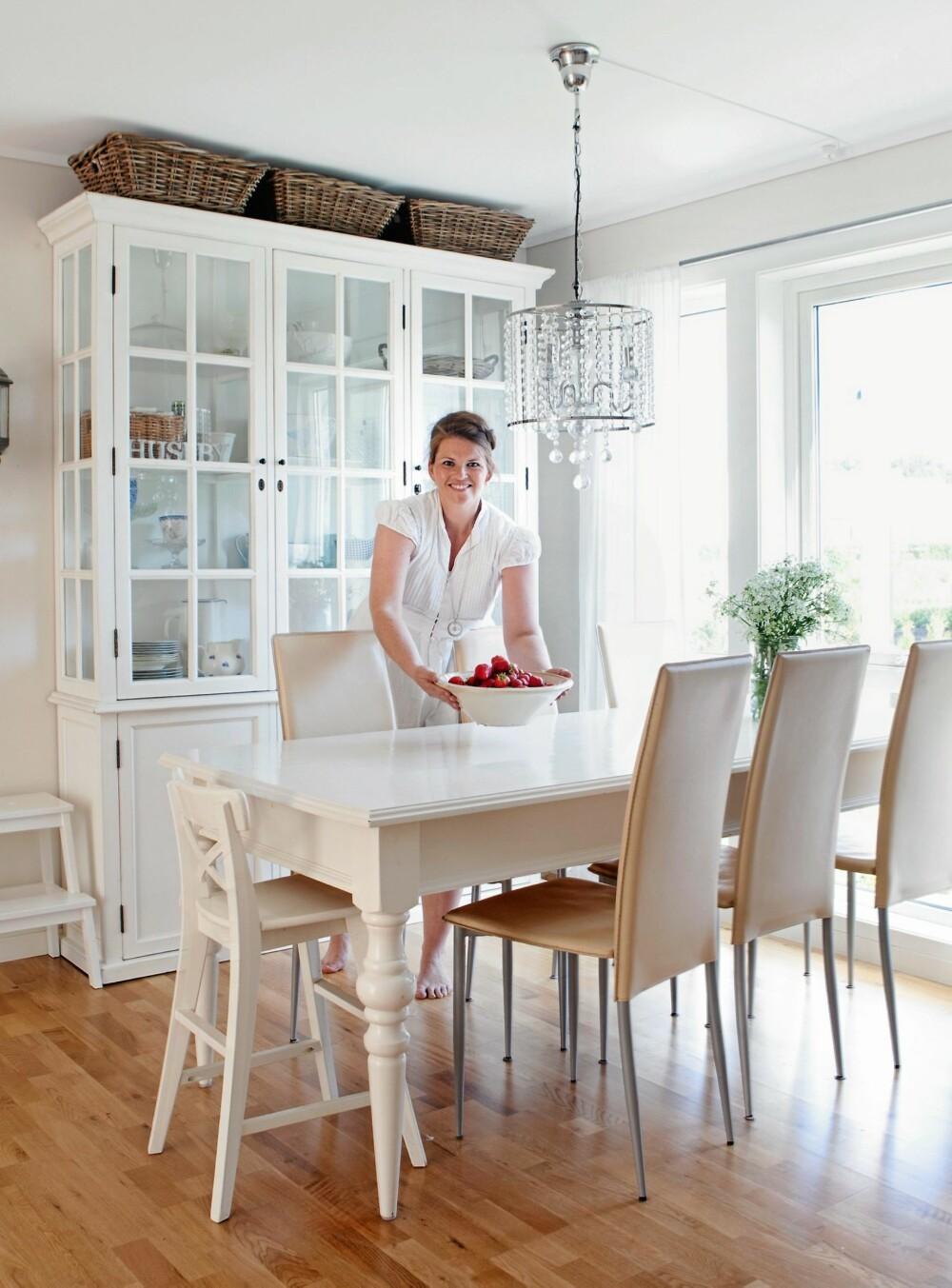 """VITRINELYKKE: Hanne Mette elsker vitrineskapet sitt, og endrer """"utstillingen"""" etter sesong. Spisebordet er kjøpt i en bruktbutikk, mens stolene er fra Bolia. Lysekronen er fra interiørbutikken Lille Hvite i Risør."""
