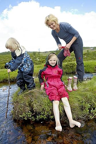 VÅTE BEIN: Mimmi tømmer Sagas gummistøvler. Mange timers lek i elva gir våte barn.
