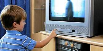 A small child watching TV with TV