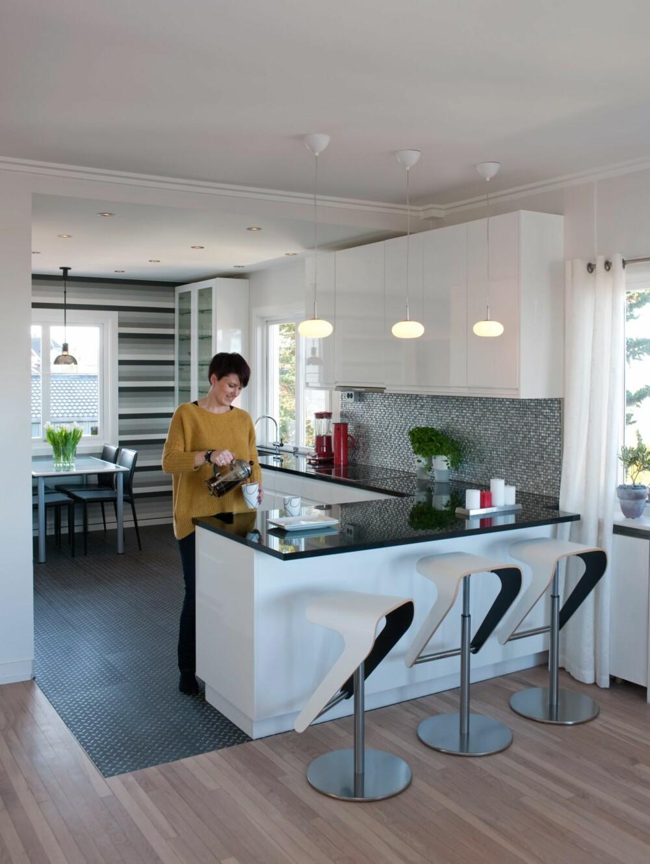 ETT ROM, TO SONER: Kjøkkenavdelingen er blitt større, og er tydelig avgrenset gjennom en barløsning og bruk av ulikt gulv. Det grafiske motivet fra tapetet gjentas i barkrakkene fra Pedrali som er hvite på utsiden og svarte på innsiden, noe som også gir dem et luftig preg.