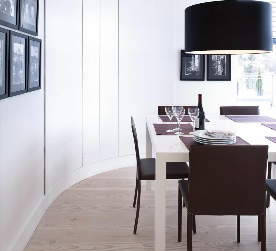 STOR PENDEL: Når rommet har en særegen form, jobb med den, ikke imot den. Her tar den overdimensjonerte pendelen opp stuens vakre buede form. De små bildenehenger i grupper på veggen,men ikke i selve buen.
