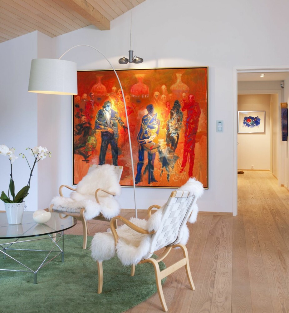 KUNSTPLASSERING: Møbler i lyse farger konkurrerer ikke med Håkon Blekens maleri Skandale i selskapslivet. At bildet er plassert lavt på veggen, skaper intimitet i det høyreiste rommet. Det runde bordet får fint følge av et teppe i samme form.