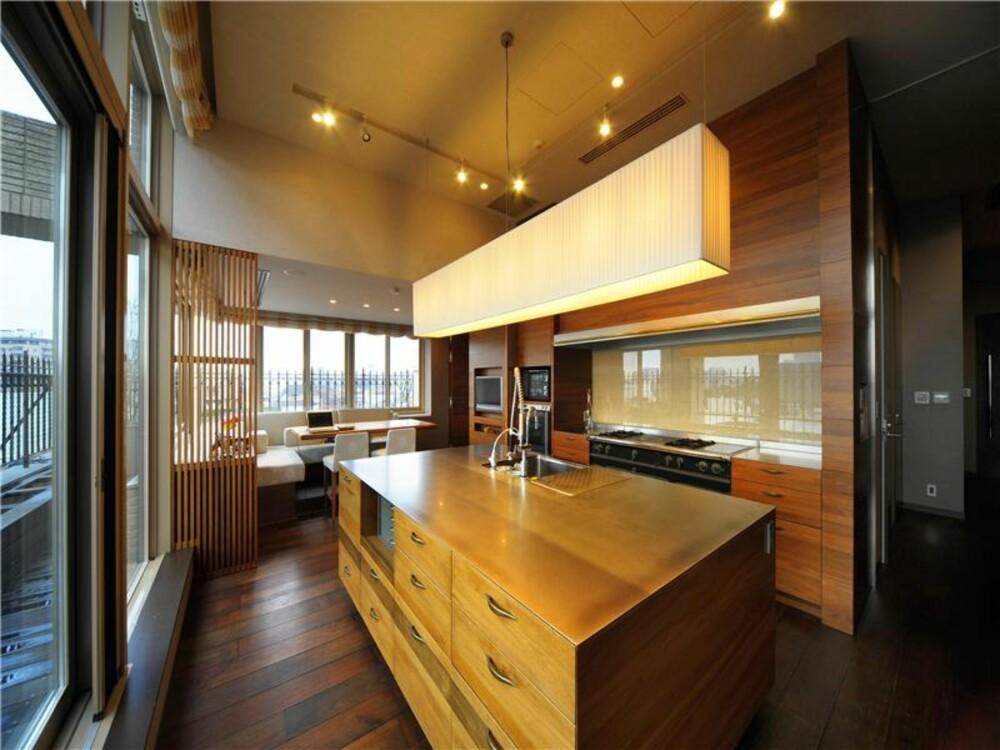 VARMT TRE: Store vinduer slipper lys og utsikt inn i leiligheten, og treverk på kjøkkeninnredningen varmer opp interiøret.