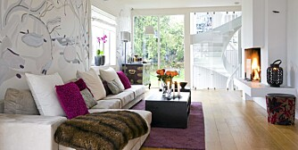 HARMONISK: Den nye, langsmale stuen ble møblert med en matchende, fem meter lang sofa. Delikat, leken dekor på bakveggen. Utsikt til trapperom kledd med glassplater.