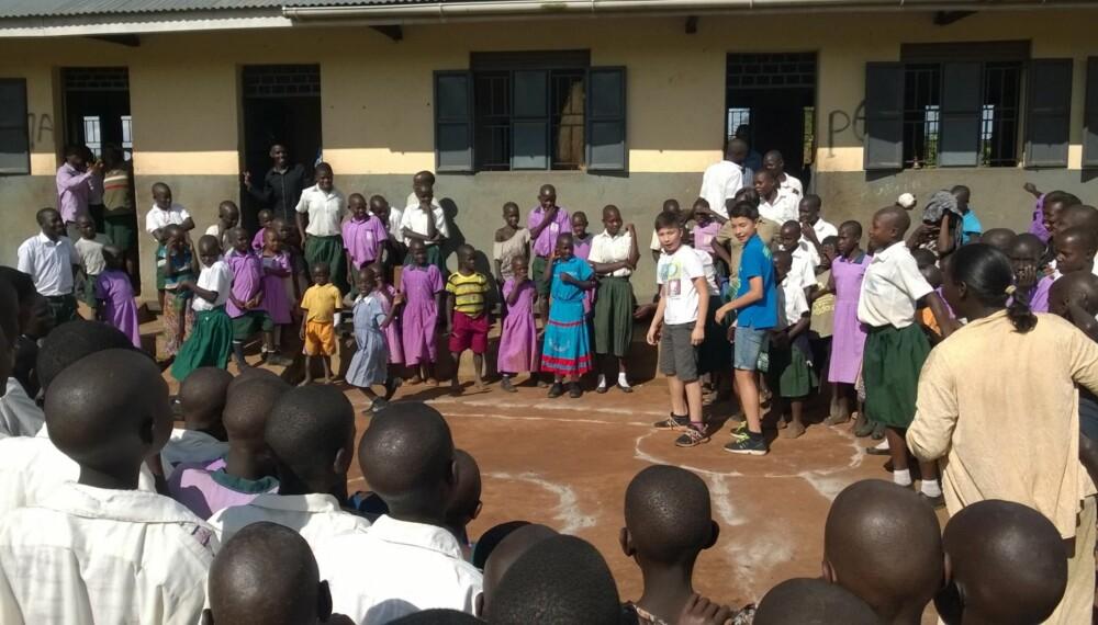 LEK OG MORO: Even og Erlend besøkte Uganda sammen med Redd Barna.De prøvde seg på ugandiske leker i friminuttet. Vanskelig, men de fikk god oppbacking av elevene!