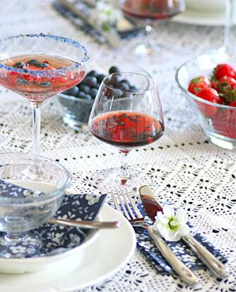 RØD BRUS: Glass med rød brus og et par blåbær oppi er både artig og annerledes. Her har interiørblogger Marianne de Bourg dekket et bord på en vakker, heklet duk.