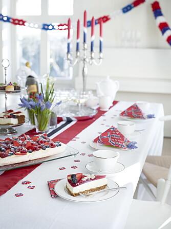 DELIKAT: Et lekkert 17. mai-festbord med løper over hvit duk. Her er det pyntet med løkblomster fra hagen og flaggservietter og lys fra Tilbords.