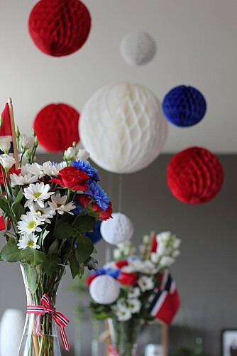 POMPOMS: - Jeg pyntet bordet med blomster i rødt, hvitt og blått og flagg  på hver ende av langbordet. I taket hang jeg opp pomponger i Norges nasjonalfarger, noen fra Kremmerhuset og noen fra Søstrene Grene for å få de i flere forskjellige størrelser, forteller instagrammer Linn Merete Skaare.