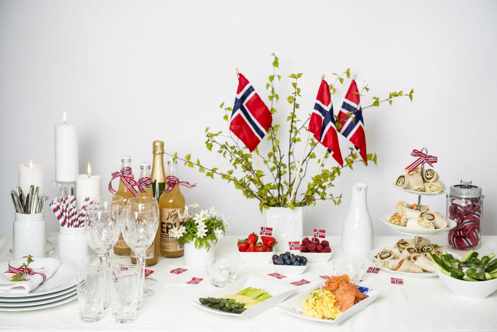 KOLDTBORD: - Maten skal stå i sentrum på 17. mai, fastslår Stine Rydningen, visual merchendiser hos Christiania Glassmagasin. Dette lekre koldtbordet er dekket med bjørkekvister og flagg i en vase, en søt bukett hvitveis og sløyfebånd i det norske flaggets farger. Produkter fra Christiania Glasmagasin.