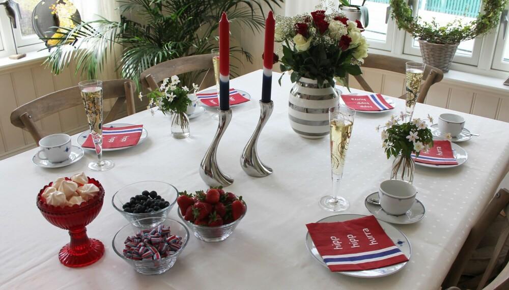 FESTBORD: Rødt, hvitt og blått er obligatoriske farger når man dekker et festbord til 17. mai. Bordet er dekket med serviset Ministrå fra Christiania Glasmagasin, champagneglass fra Ritzenhoff og servietter fra Kremmerhuset. Det er pyntet med roser i den populære Omaggio-vasen fra Kähler og Cobra lysestakene er fra Georg Jensen og selges blant annet hos Tilbords. I skålene på bordet godter i det norske flaggets farger - jordbær, blåbær, norgesdrops og makroner.