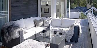 KONVENSJONELT: Terrassen er innredet med ordinære flettmøbler, men gitt et personlig preg ved bruk av puter og pledd.