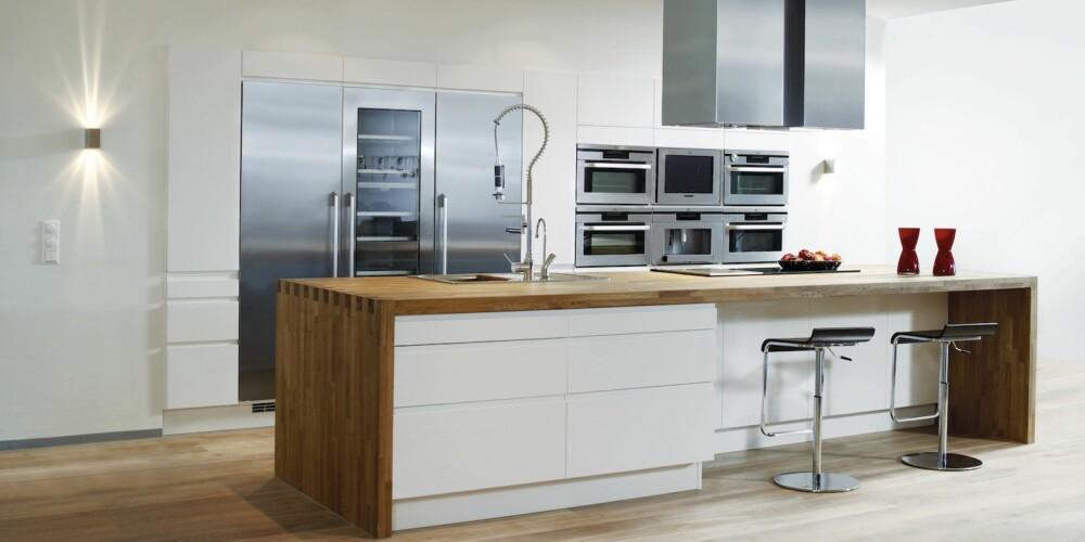 TRENDY: I dette minimalistiske kjøkkenet kan du underholde familien mens du lager mat.
