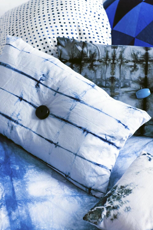 MODERNE UTTRYKK: Batikk skaper et moderne og avslappet uttrykk. På puten med den blå knappen er det brukt svart batikkfarge på grå tekstil.