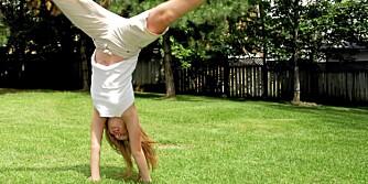 Jente slår hjul på gresset.
