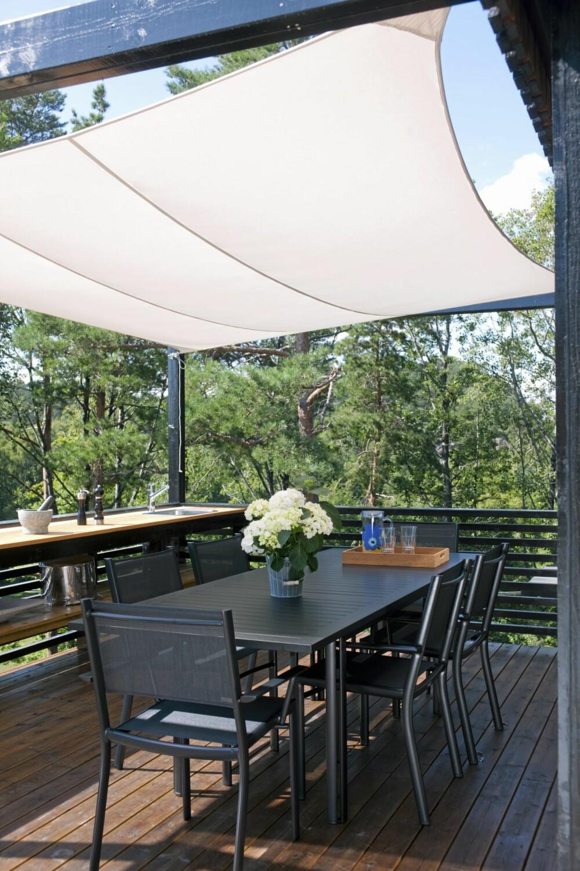 UTNYTTER UTEROMMET: Solseilet skjermer for både sol og trekk på terrassen med utekjøkkenet. Slik forlenges sesongen ute med flere uker.