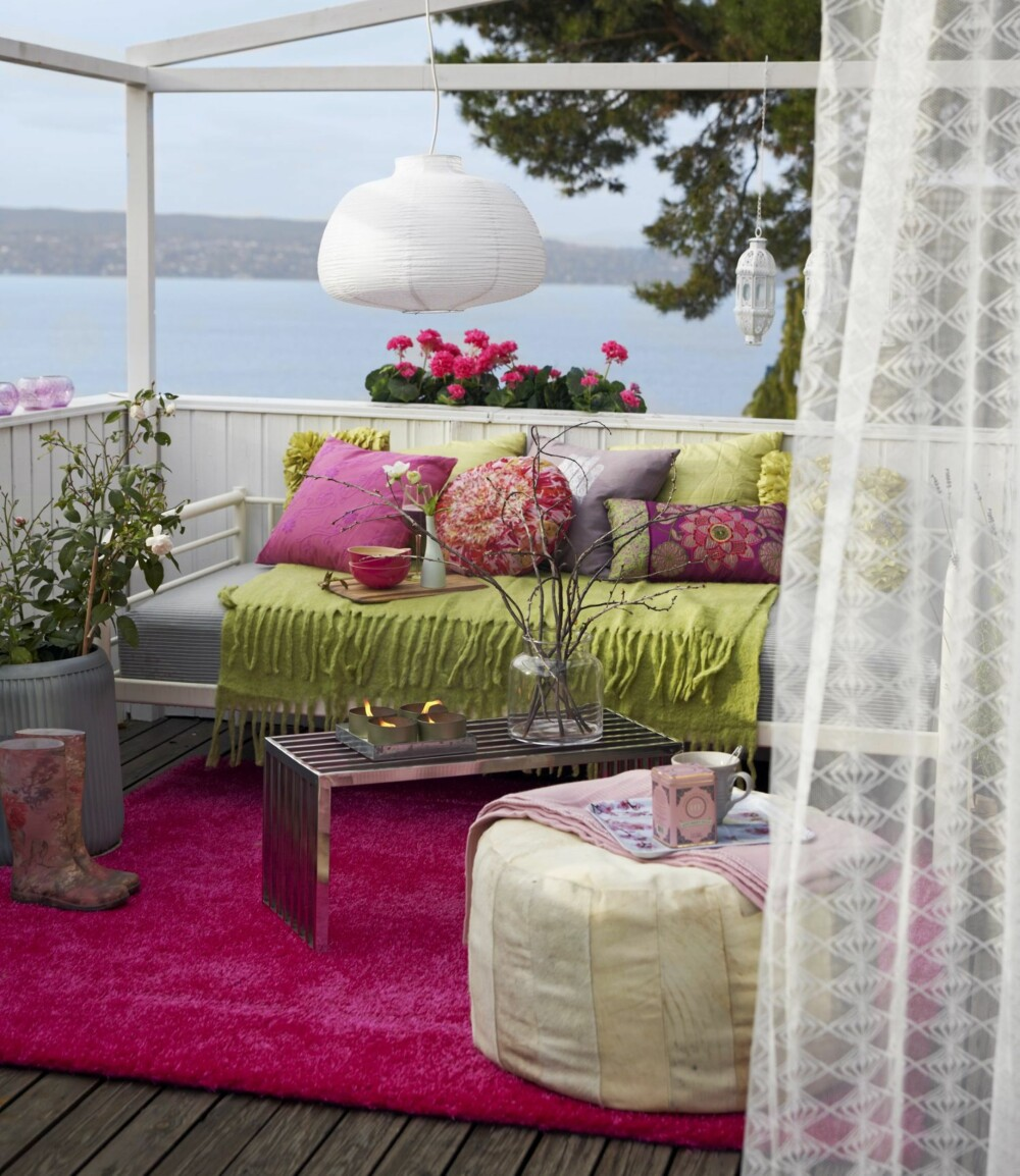 FARGERIKT UTEROM: Terrassen er innredet med et rosa gulvteppe, og en sofa full av puter i ulike farger og mønstre. Detaljer som blomster, levende lys og lampen over salongbordet gir uterommet et stuepreg.