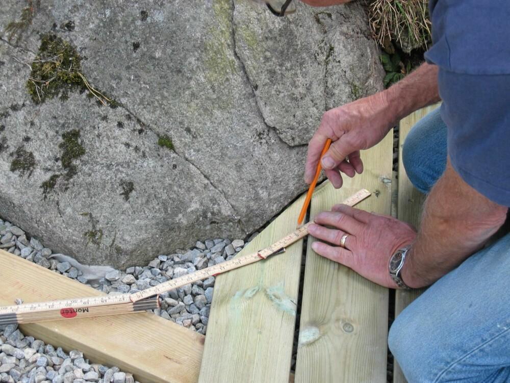 TILPASNING MOT FJELL: Det blir penest og mest praktisk om terrassegulvet støter mot fjellknausen med minst mulig avstand. Ved hjelp av knekken på meterstokken, avsettes riktig bue på enden av trerrasebordene, slik at de blir formet etter fjellet.