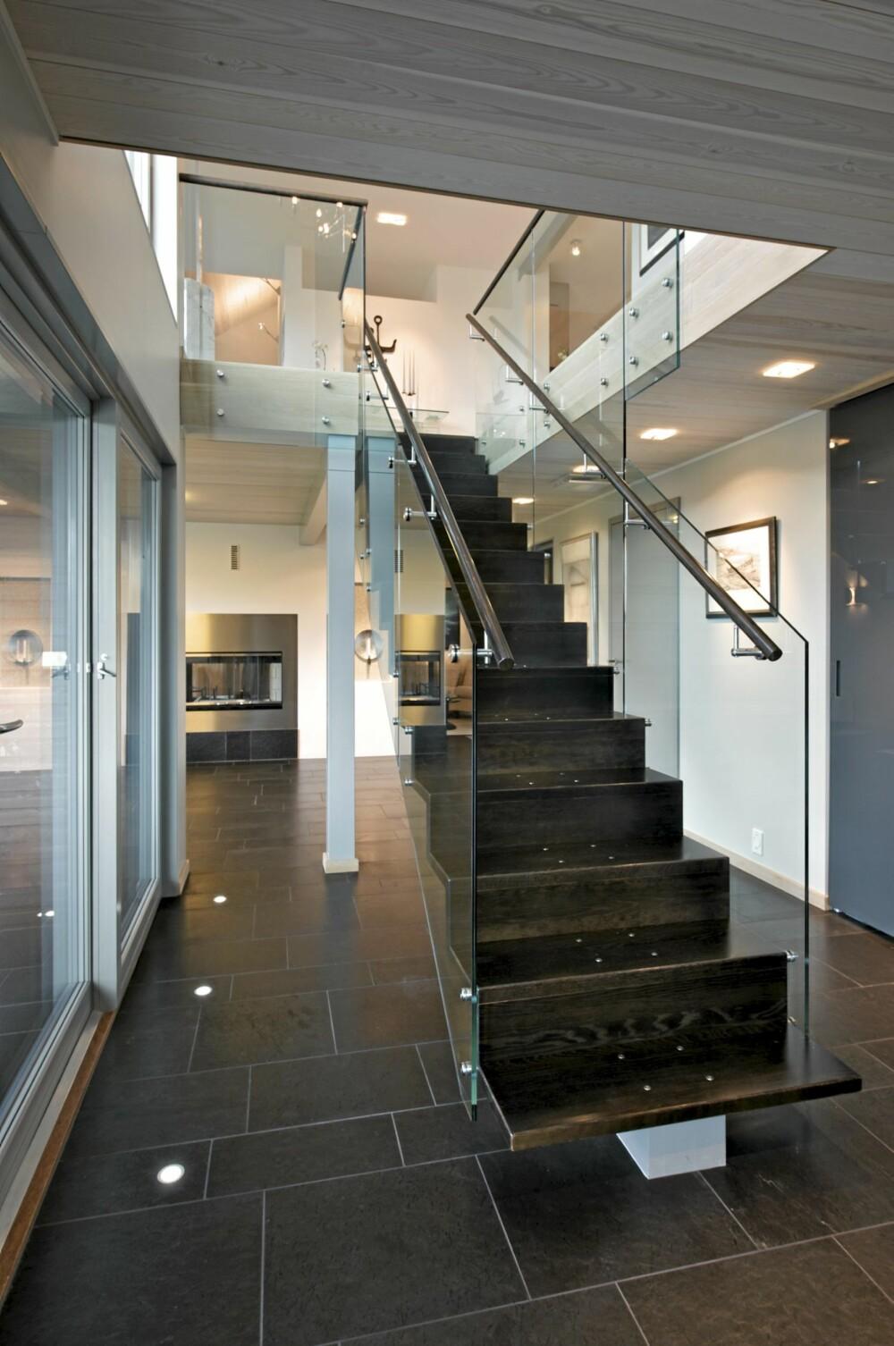 RETT TIL TOPPS: Fra trappen i hallen går ferden rett opp til kjøkkenet med de mørke eikefrontene. Legg merke til de gjennonførte detaljene i trappen.