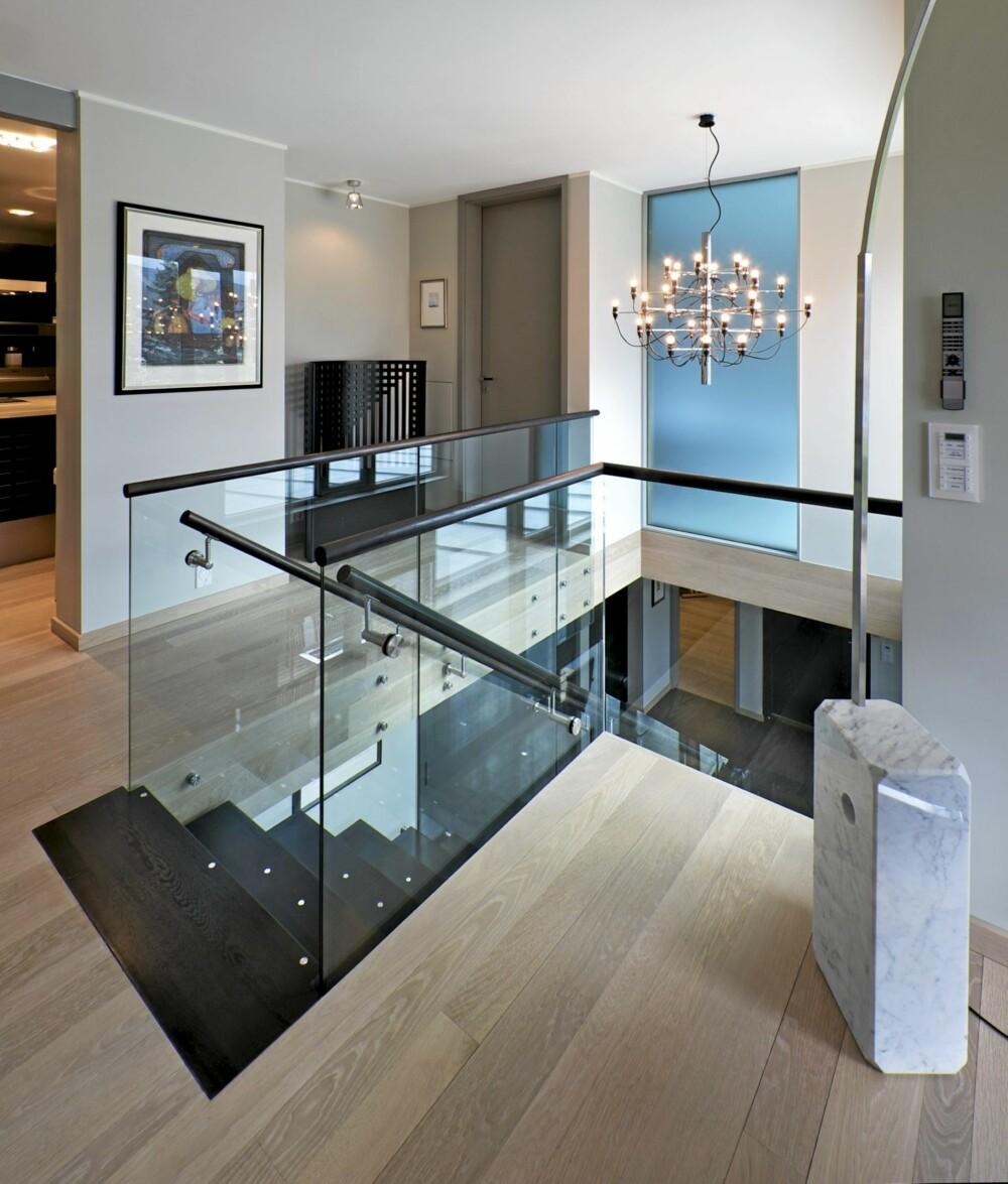 """HØY PÅ DESIGN: Med et trapperom som åpner for lyset og et tilstøtende """"glassgalleri"""" åpnes rommene for lyset. Italienske lampeklassikere og designmøbler kler rommet. Lys eik på gulvet."""