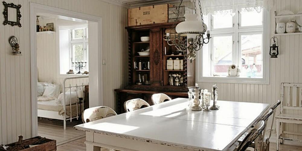 NOSTALGI: De hvite omgivelsene er preget av nostalgi og sjarm. Stolene rundt spisebordet ser ut til å være godt brukt i årevis, og hyllene i sjenken er fylt med gamle krukker og kar.