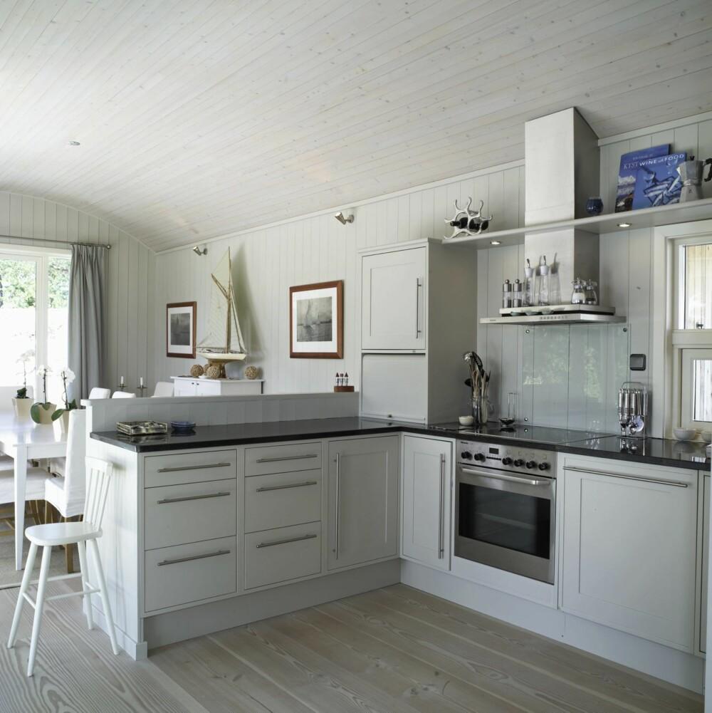LETTE FARGETONER: Kjøkkenet i den enne enden av hytta er også holdt i den enkle, lette stilen som preger stedet. Den rolige gråfargen du ser er spesialblandet, og den går igjen i flere rom i disse sommerhusene.