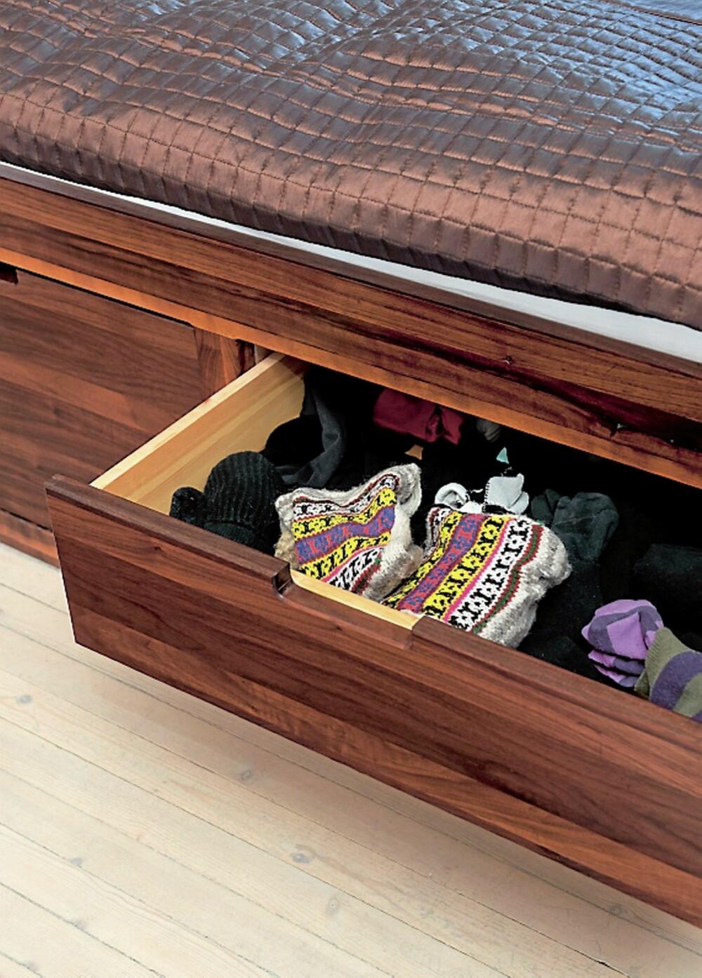 UNDER SENGEN. Sengen i valnøtt har fem skuffer på hver side som vanligvis skjules av sengeteppet. Sengen hadde beboerne fra før, den er i solid valnøtt, tegnet av møbelsnekker Jana Toneff. Hun har også har laget den nye garderobeløsningen.