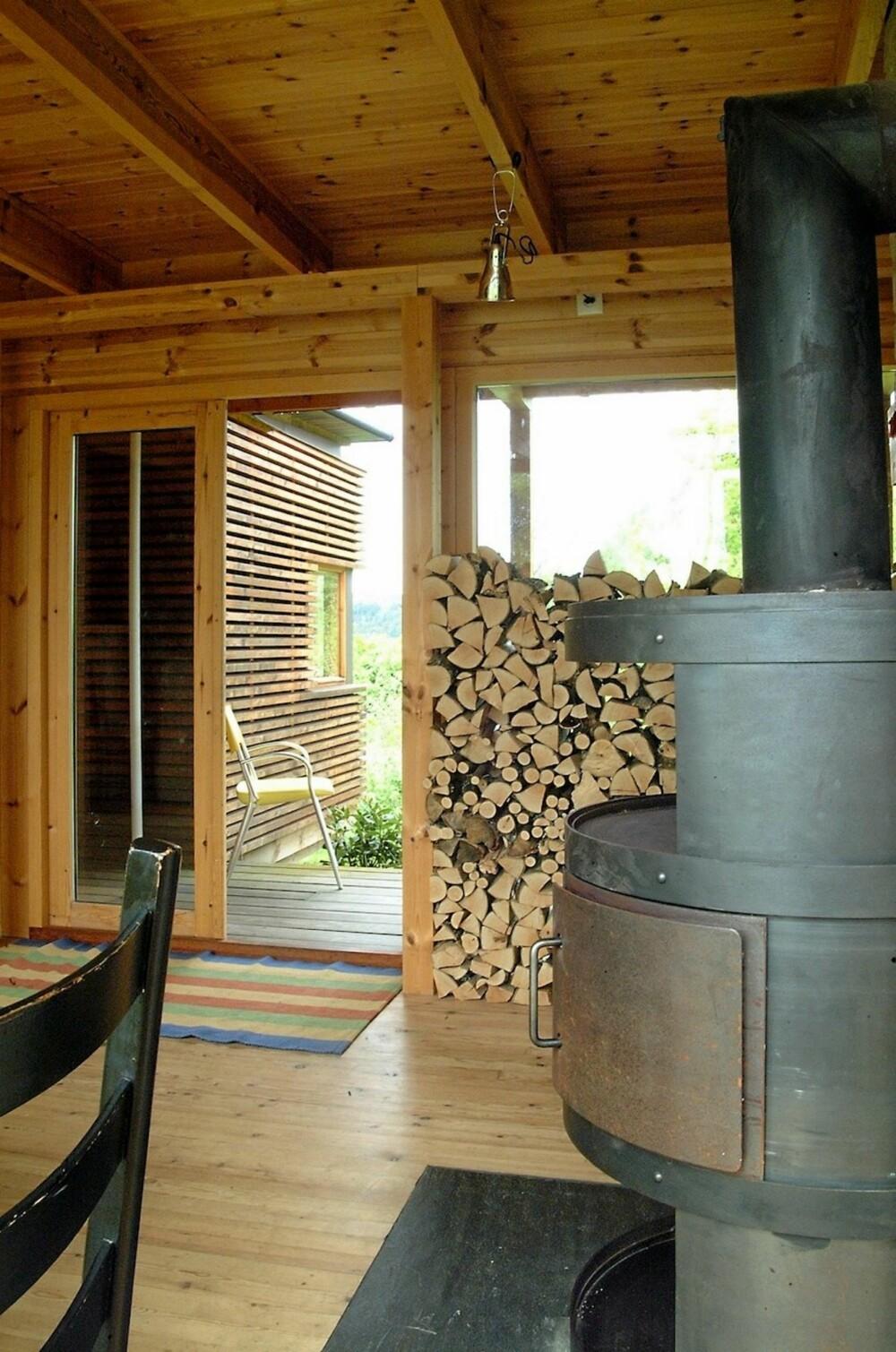 ET UTMERKET INTERIØR SAMSPILL: Peisovnen, vedstabelen og den lette trekonstruksjonen i hytta passer sammen.