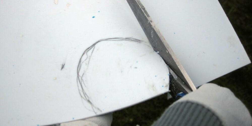 PLAST: Klipp av en plastbit fra en plastkanne eller et malingspann. Klipp ut en runding som er litt større en kjernen på rulla