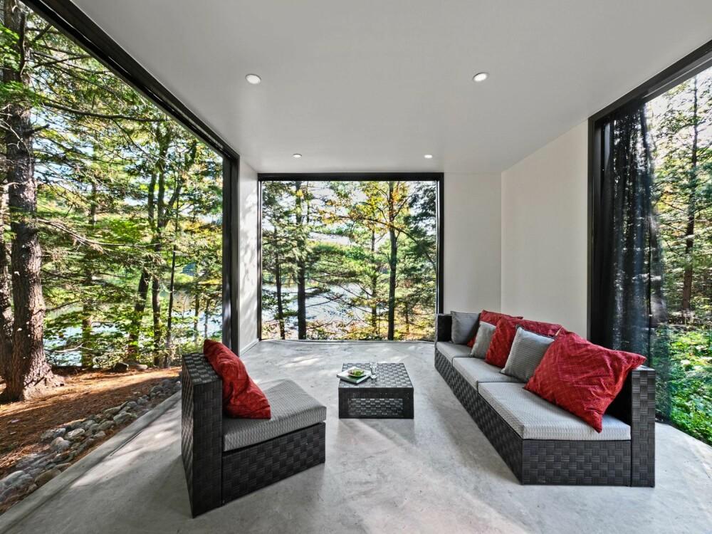 STUE: Stuen er en del av fellesområdet i hytta. Oppholdsrommet er omsluttet av glassvinduer