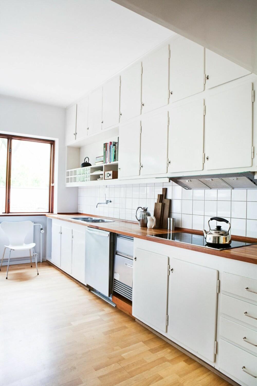 LIKE FINT: Kjøkkenet er originalt, håndsnekret og hvitmalt. Overalt er det innebygget skap og skuffer. Kannene er fra Stelton, kjele av Sori Yanagi fra Gateway Japan.