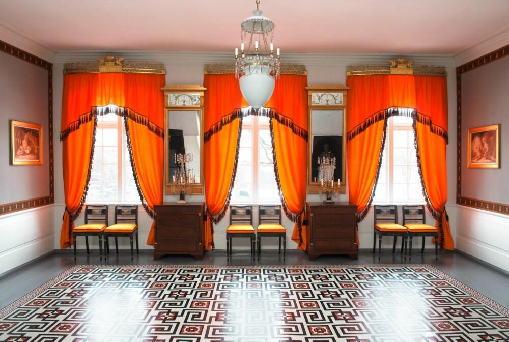 SKIKK OG BRUK: Familien Ankers spisestue var møblert med tolv stoler langs veggene og kommoder mellom vinduene. På den tiden var ikke bord en fast del av innredningen, men ble båret inn når det skulle brukes. På gulvet, et såkalt voksdukteppe. Gardinbrettene er fra herskapshuset Paleet i Oslo og kom til Eidsvoll omkring 1900. Possementene på gardinene stammer også derfra, de er rekonstruert i England.