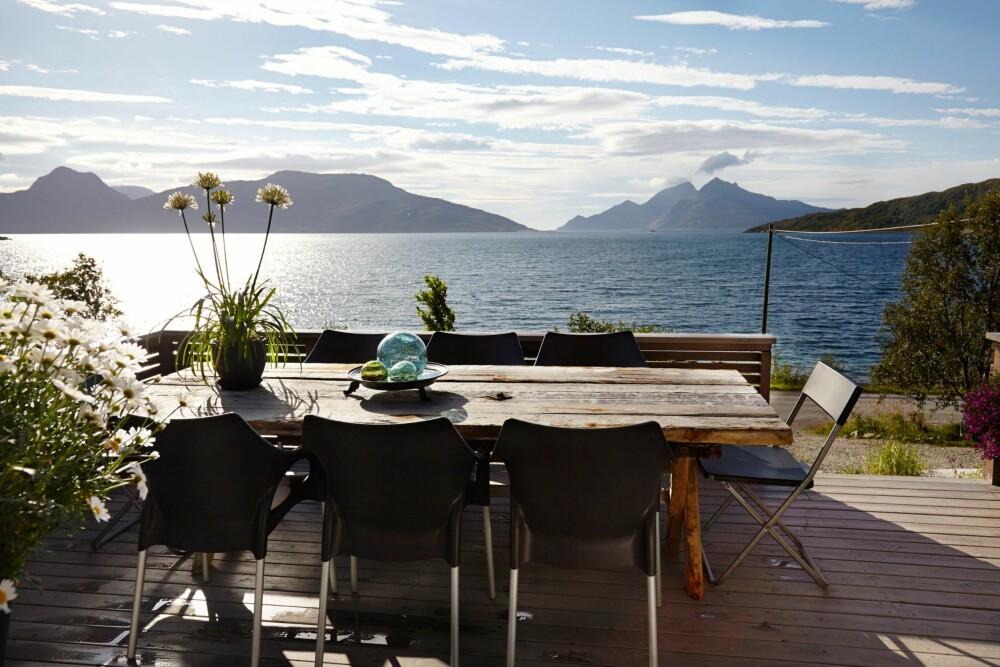 UNIK SPISEPLASS: Det er plass til mange gjester ved det store spisebordet. Den åpne fjorden og de majestetiske fjellene skaper en vakker ramme rundt måltidet.