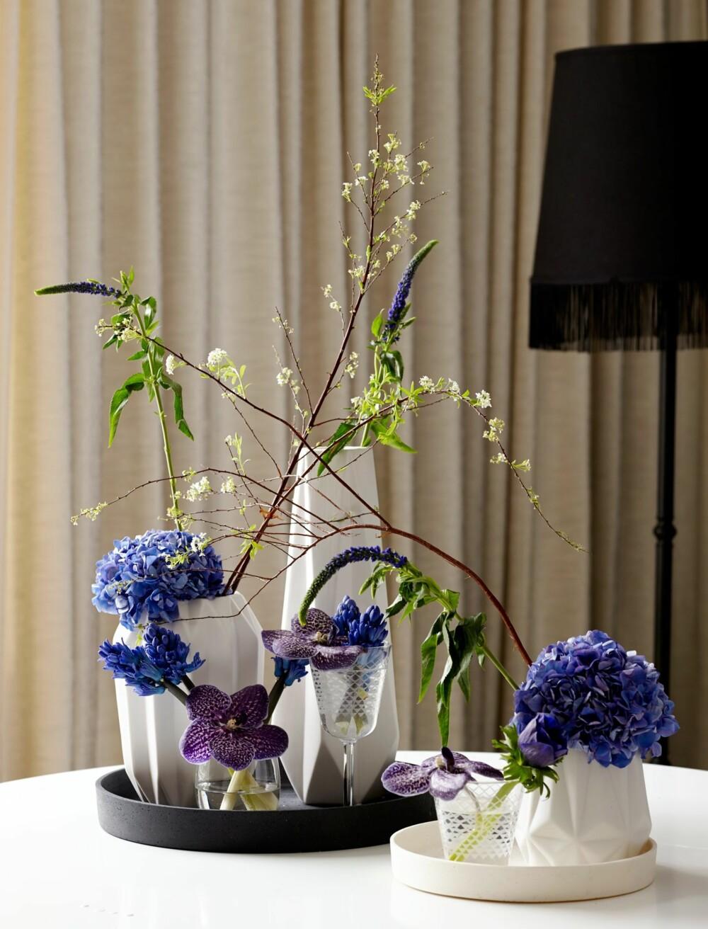 PÅ FAT: Ulike vaser og glass fordelt på to fat, danner basen for denne borddekorasjonen.  Her ser du hortensia, hyacinter og veronicea i blåtoner, som går mot lilla i wandaorkidéene.  Takk til Åhléns for lån av kanner, vaser og fat.Idé og styling: Juni Hjartholm/Steen & Aiesh for Bonytt.