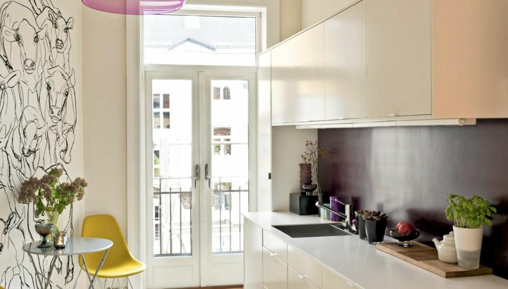 """MODERNE MIKS: Marimekko-tekstilet """"Kevatjuhla""""(Vårfest) dekker hele kjøkkenveggen og gir liv til hele leiligheten. Auberginefargen trengte seks(!) strøk for å bli dyp og tett nok i strukturen. To Vitra """"Plastic Chair""""."""