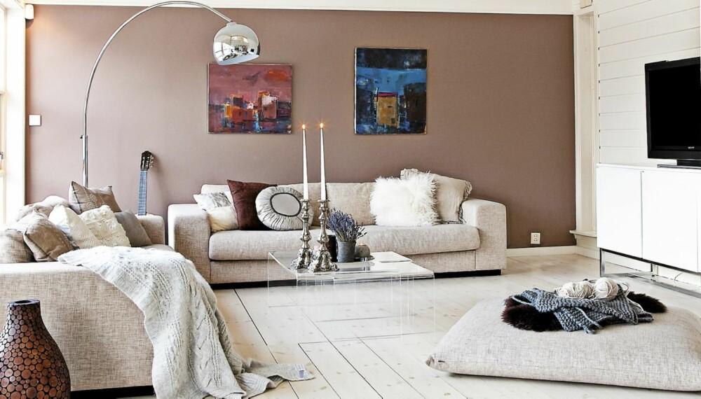 NY STIL. Villaen fra 80-tallet er blitt lysere og luftigere. Tv-stua er utstyrt med sofaer fra Bolia samt stor sittepute på gulvet. Bildene på veggen har Britt Schlytter-Henrichsen malt.