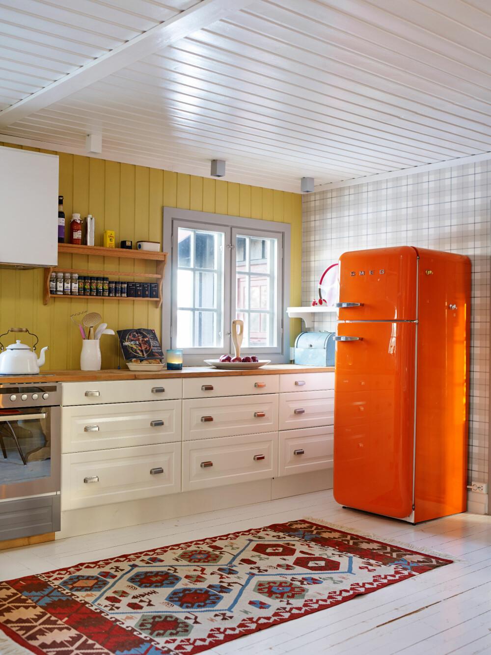 LUN OG GLAD: At Anette blir glad av å være på hytta, skjønner vi godt. Med farger har hun skapt en oppkvikkende atmosfære. Kjøleskap fra Smeg. Da de utvidet kjøkkenet, skaffet de ekstramoduler fra Ikea.
