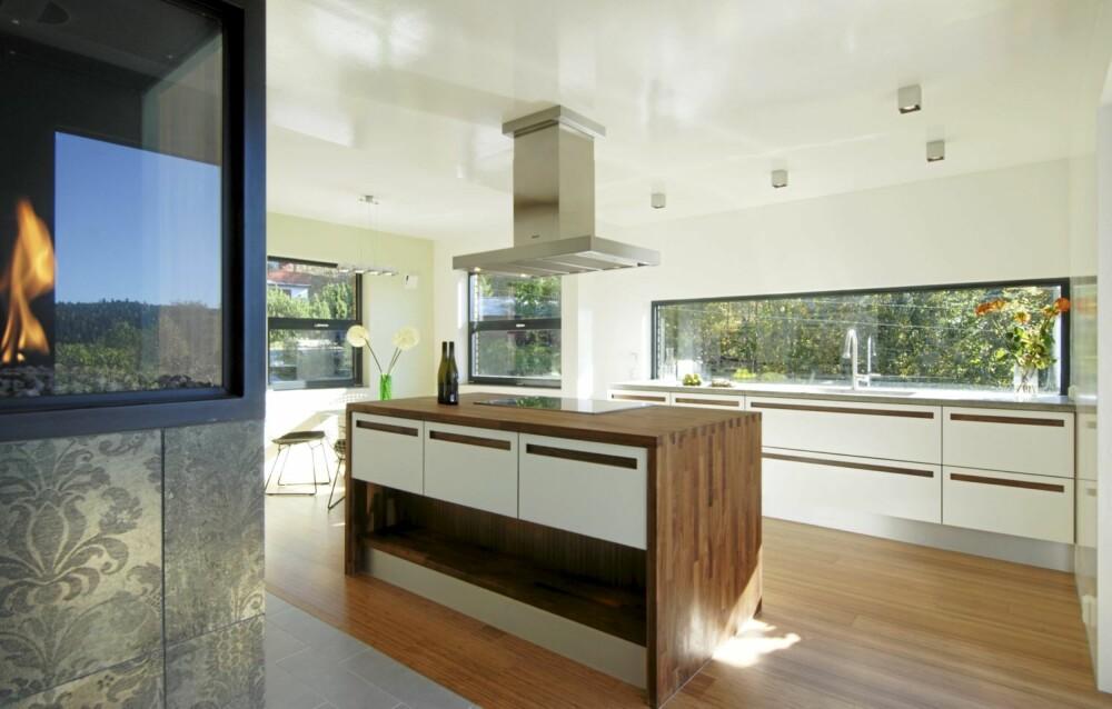 SONE FOR TRIVSEL: Med kjøkkenøya midt i rommet og glass hele veien rundt samt fyr på peisen er dette kjøkkenet et sted for trivsel.
