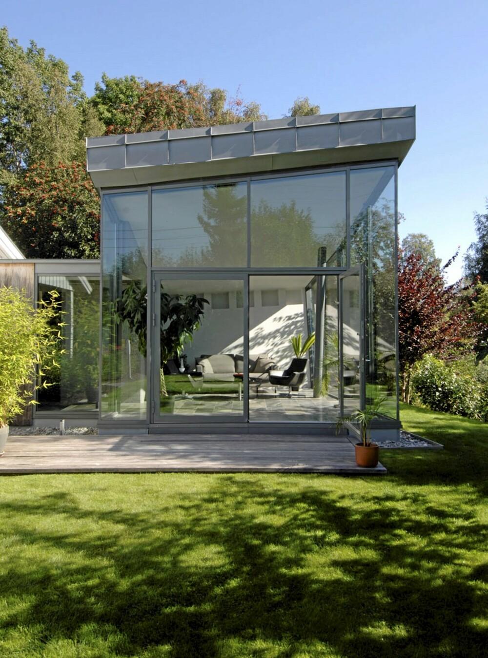TOTALT FRISLEPP: Det arkitekttegnete tilbygget, hagestuen åpner seg maksimalt mot solen. Bygningen måler nesten fire meter på det høyeste og vel to meter på det laveste. Vinduene er satt inn i smekre, ikkebærende stålrammer som ikke stjeler noe av utsikten. De gir soliditet til den enorme glassfasaden, men det er de kraftige søylene  lenger inn i rommet og bakveggen i betong som bærer  konstruksjonen. Glasset fortsetter også rundt hjørnet til venstre mot mellomgangen og hovedhuset.