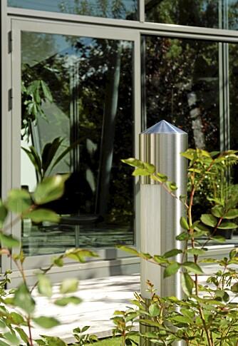 MATCHENDE MATERIALER: Både lyssøylen og dørstopperne er laget i solid, rustfritt stål - og selvfølgelig i en stil som matcher tilbygget.