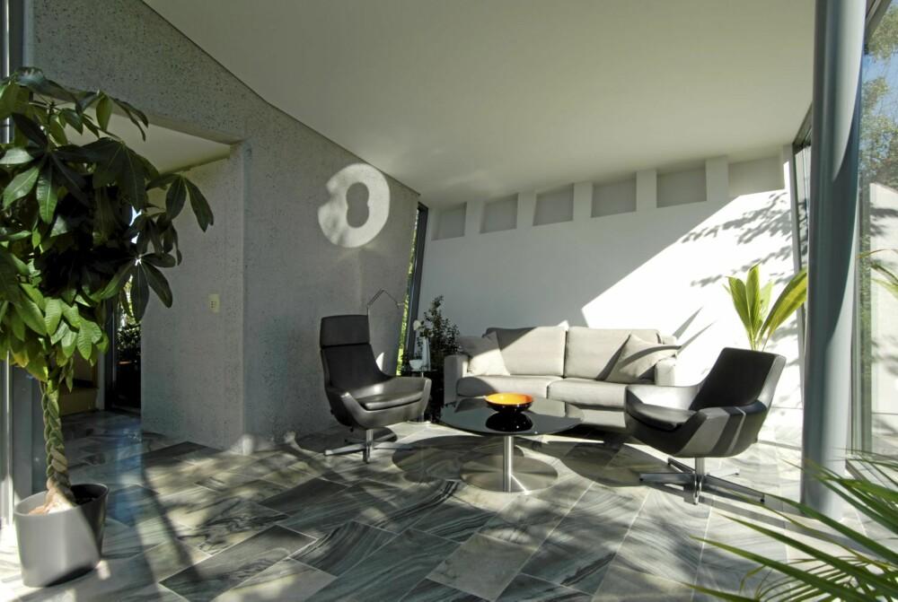 HELÅRS LYSTHUS: Oppgaven til arkitekten var å lage et sommerlig lysthus, men med gulvarme og gode UV-verdier på glassfasaden kan rommet brukes hele året. Her ser du den bærende betongveggen i bakkant av stuen. Samme hvitfarge på vegg og tak gjør at disse to elementene oppleves nesten som en flate.