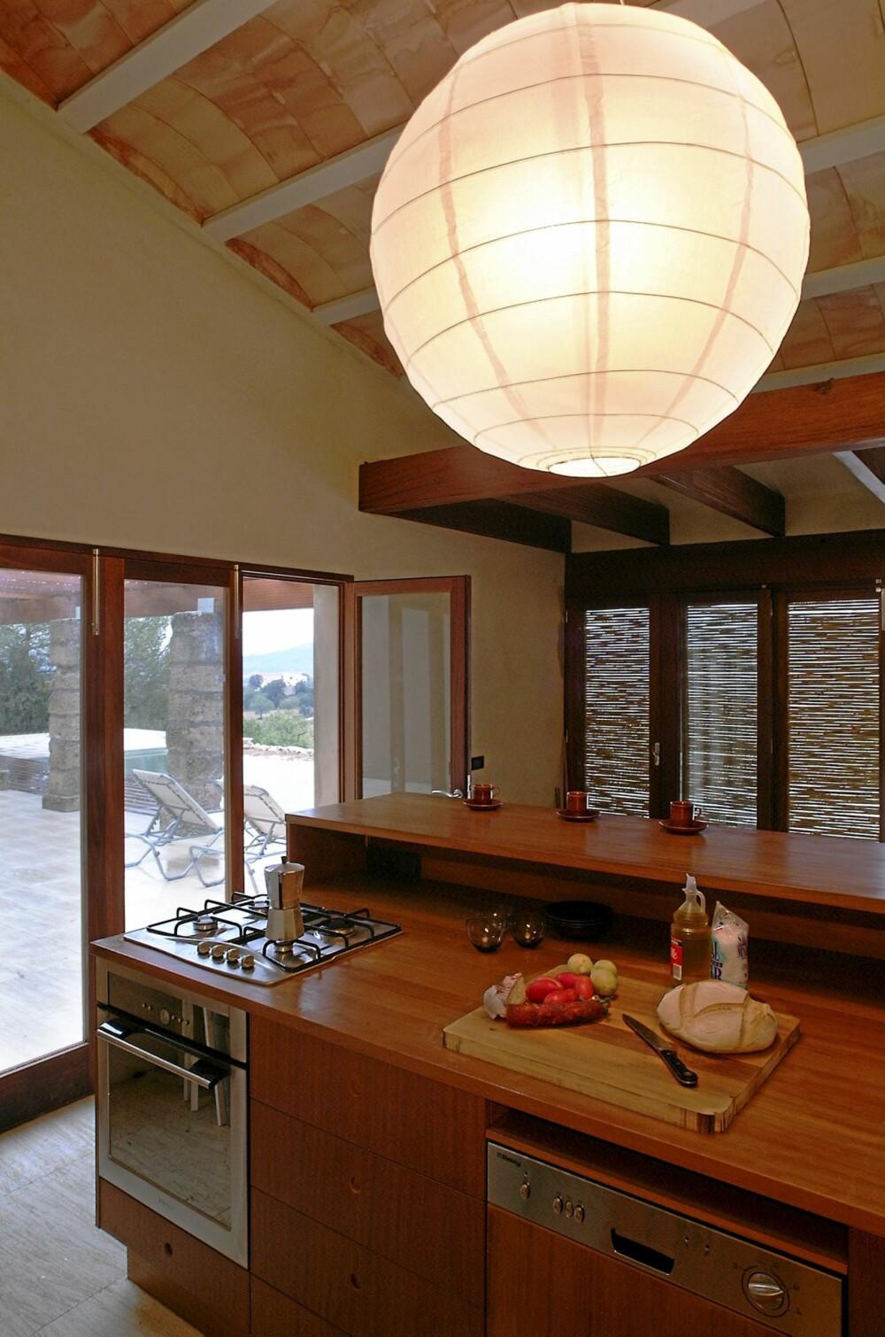 ÅPEN SONE: Kjøkkenet åpner seg også totalt mot utsikten og rommet har en solid og effektiv øy-innredning. Veggene er malt i en lys, tobakksaktig valør.