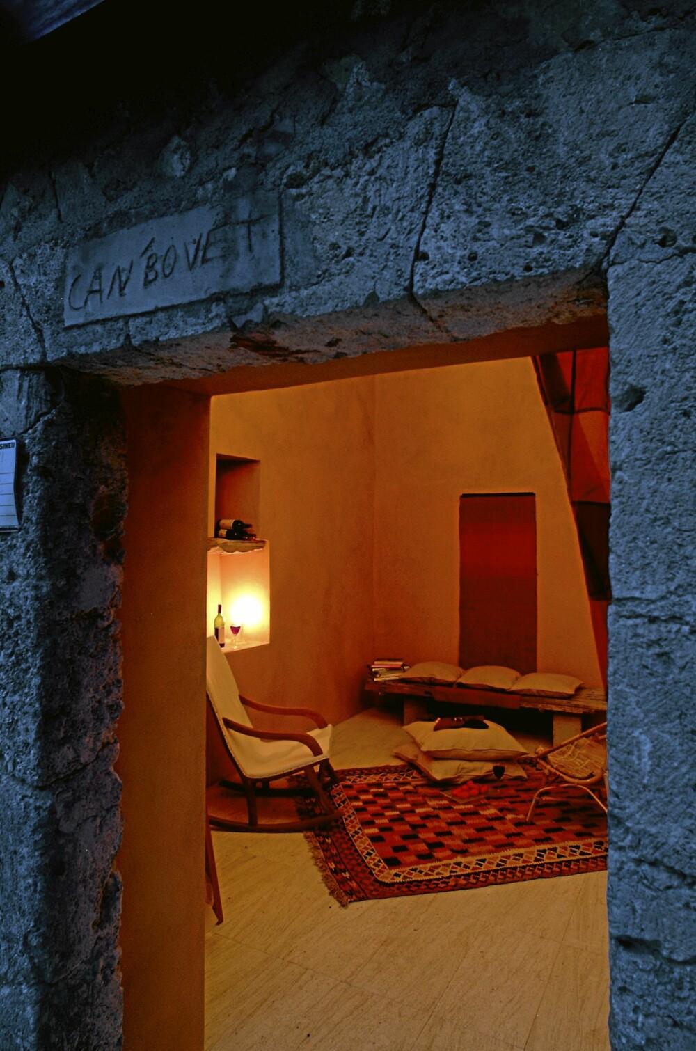 """RO I RUIN-ROMMET: Det gamle fjøset; Càn Bovet, """"Huset til den lille oksen"""", er et herlig, stemningsfullt sted på 35 kvm med en blanding av nytt og gammelt. Her er det grove vegger mot myke, berberaktige møbler.Vegger malt i en appelsinaktiv oransjefare. Rommet lukkes med en skyvedør i glass."""